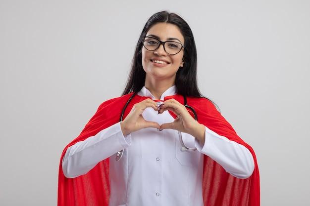 Lächelnde junge superfrau, die brille und stethoskop trägt, die front tut, die herzzeichen lokalisiert auf weißer wand tut