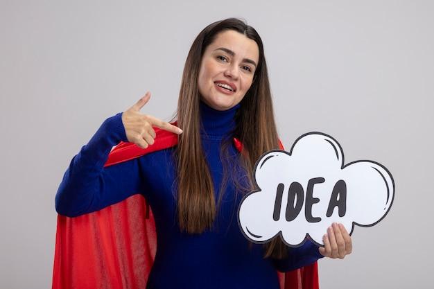 Lächelnde junge superheldenmädchen halten und zeigt auf ideenblase lokalisiert auf weißem hintergrund