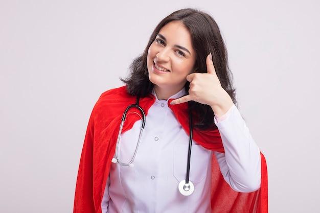 Lächelnde junge superheldin in arztuniform und stethoskop, die nach vorne schaut und anrufgeste isoliert an der wand macht