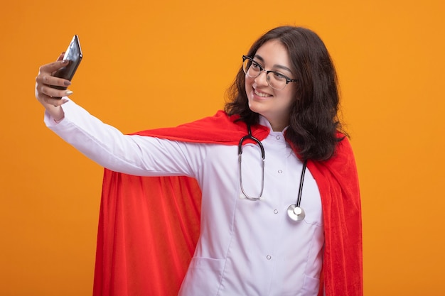 Lächelnde junge superheldin in rotem umhang in arztuniform und stethoskop mit brille, die selfie isoliert auf oranger wand macht