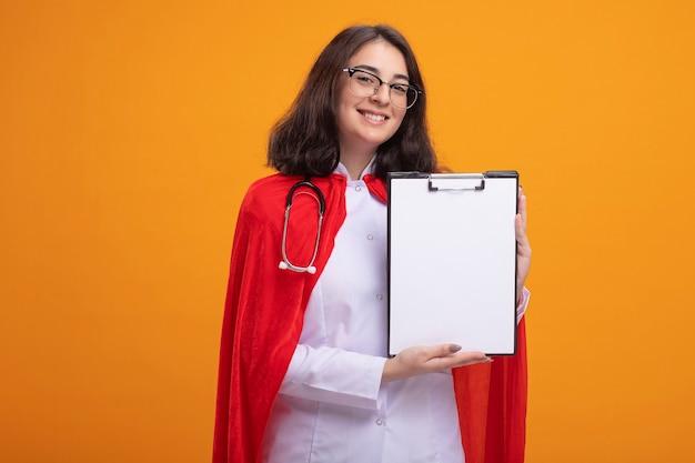 Lächelnde junge superheldin in rotem umhang mit arztuniform und stethoskop mit brille, die die zwischenablage nach vorne zeigt und auf die vorderseite isoliert auf der orangefarbenen wand blickt