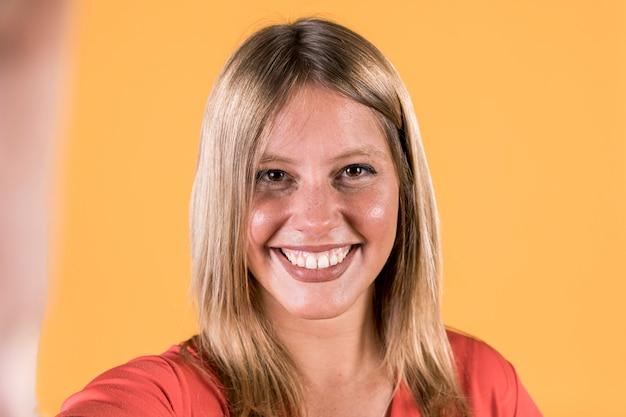 Lächelnde junge taube frau, die selfie gegen gelben hintergrund nimmt
