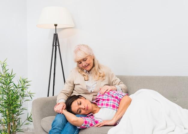Lächelnde junge tochter, die auf dem schoss ihrer älteren mutter sitzt auf sofa schläft