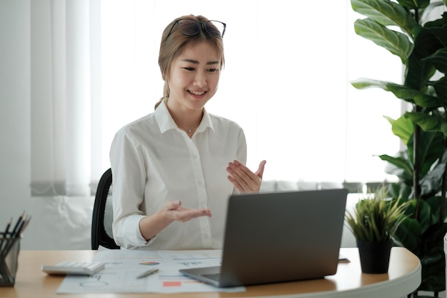 Lächelnde junge weibliche angestellte zu hause sprechen über videoanrufe auf dem laptop mit verschiedenen kollegen. asiatische arbeiterinnen haben eine webcam-konferenz oder ein digitales web-team-meeting oder briefing mit kollegen.