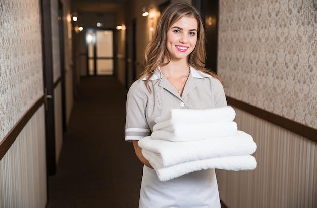 Lächelnde junge weibliche haushälterin, die gefaltete tücher im hotelkorridor trägt