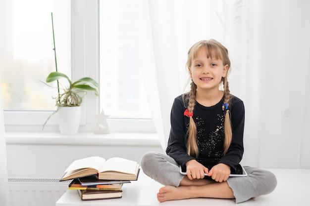 Lächelnde junge weibliche kinder mit digitalem tablet-pad, die online-e-learning-videos ansehen, um zu hause englisch zu lernen