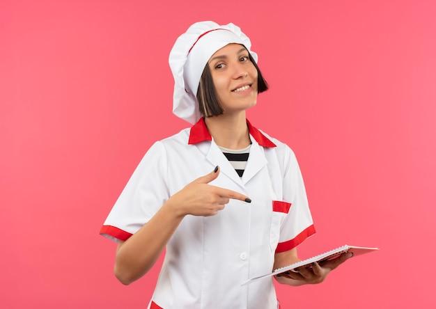 Lächelnde junge weibliche köchin in der kochuniform, die auf notizblock lokalisiert auf rosa wand hält und zeigt