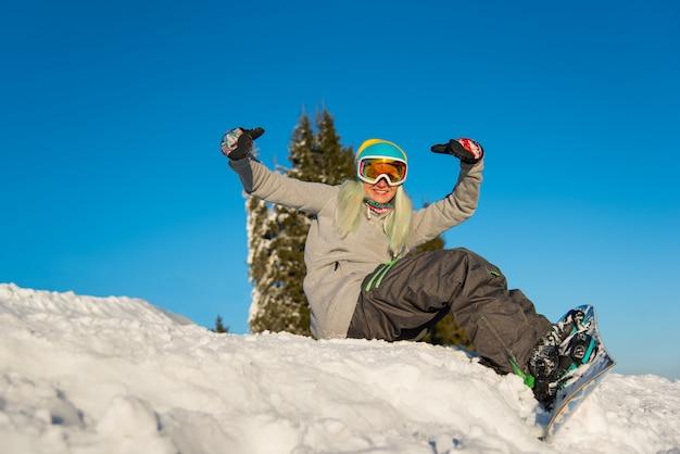 Lächelnde junge weibliche snowboarderin, die an einem schönen sonnigen winterabend oben auf dem schneebedeckten hang draußen sitzt und spaß hat