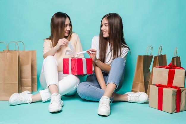 Lächelnde junge zwei mädchen, die bodeneinkaufstaschen sitzen und geschenke an der türkisfarbenen wand öffnen.