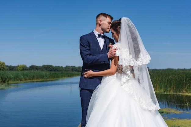 Lächelnde jungvermählten schauen sich sanft an und umarmen sich. porträt ein hochzeitspaar, das nahe fluss aufwirft.