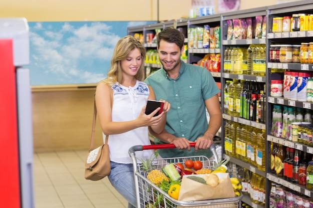 Lächelnde kaufende lebensmittelprodukte der hellen paare und notizbuch verwendend