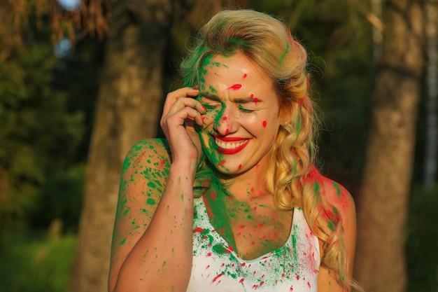 Lächelnde kaukasische blonde frau mit hellem make-up posiert mit holi-farbe bedeckt