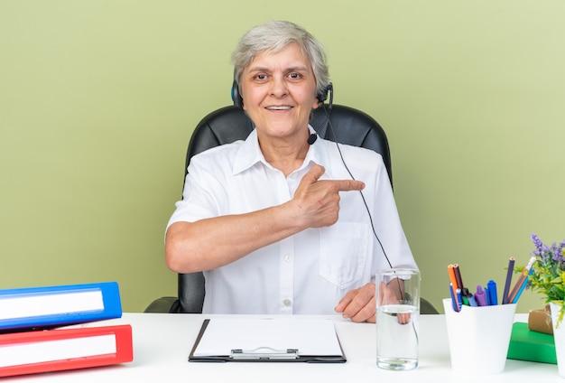 Lächelnde kaukasische call-center-betreiberin auf kopfhörern, die am schreibtisch sitzen, mit bürowerkzeugen, die auf die seite zeigen, isoliert auf grüner wand