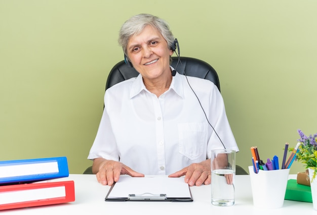 Lächelnde kaukasische callcenter-betreiberin auf kopfhörern, die am schreibtisch mit bürowerkzeugen sitzen, die die zwischenablage isoliert auf grüner wand halten