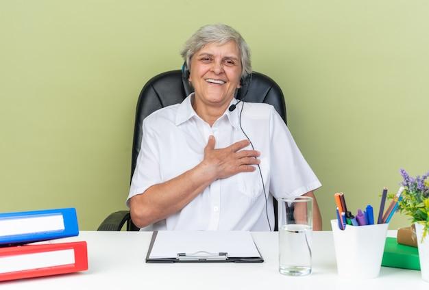 Lächelnde kaukasische callcenter-betreiberin auf kopfhörern, die am schreibtisch mit bürowerkzeugen sitzen und die hand auf ihre brust legen, isoliert auf grüner wand