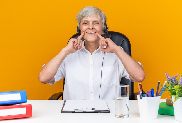 Lächelnde kaukasische callcenter-betreiberin auf kopfhörern, die am schreibtisch mit bürowerkzeugen sitzen und ihr lächeln mit den fingern halten, die auf orangefarbener wand isoliert sind
