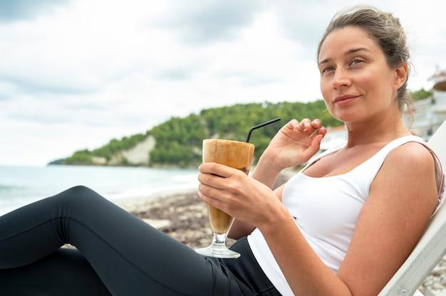 Lächelnde kaukasische frau, die kaffeegetränk an einem strand mit schaum und trinkhalm mit hügeln hält