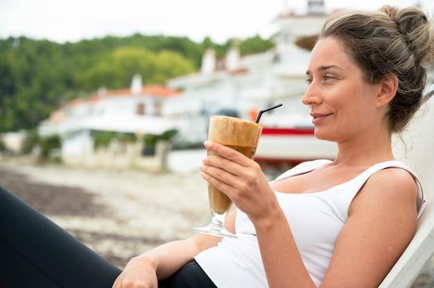 Lächelnde kaukasische frau, die kaffeegetränk an einem strand mit schaum und trinkhalm mit stadt hält