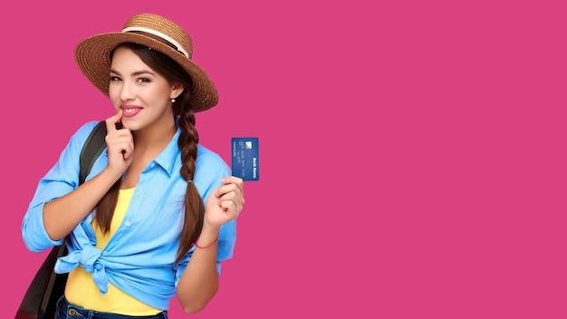 Lächelnde kaukasische frau, die kreditkarte lokalisiert auf rosa hintergrund hält. online-shopping, e-commerce, internet-banking, geld ausgeben, lebenskonzepte genießen