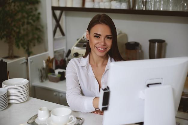 Lächelnde kaukasische frau hinter der bar, in einem arbeitsablauf hinter einem monitor