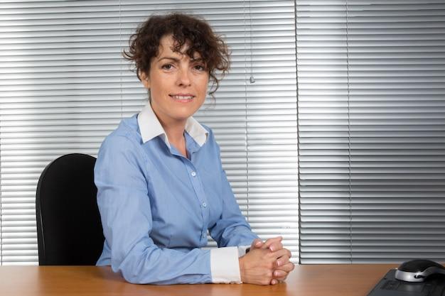 Lächelnde kaukasische geschäftsfrau, die im büro sitzt und die kamera betrachtet
