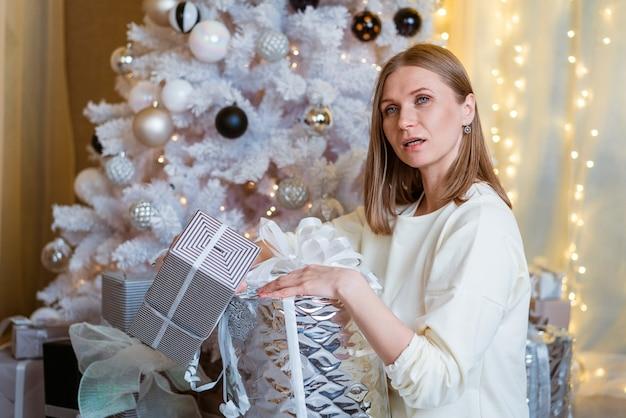 Lächelnde kaukasische junge frau öffnet kasten mit weihnachtsgeschenk weihnachtslebensstil und -einkaufen