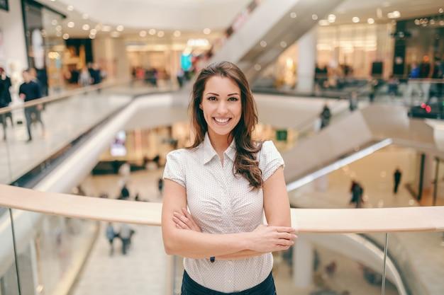 Lächelnde kaukasische niedliche brünette im hemd, das sich auf geländer stützt und arme verschränkt hält. innenraum des einkaufszentrums.