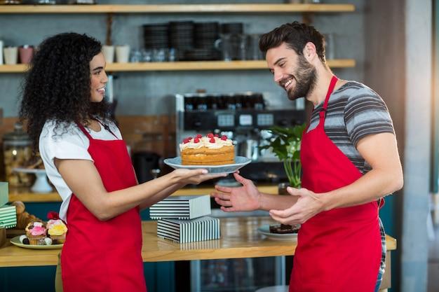 Lächelnde kellnerin, die dem kellner einen teller kuchen gibt
