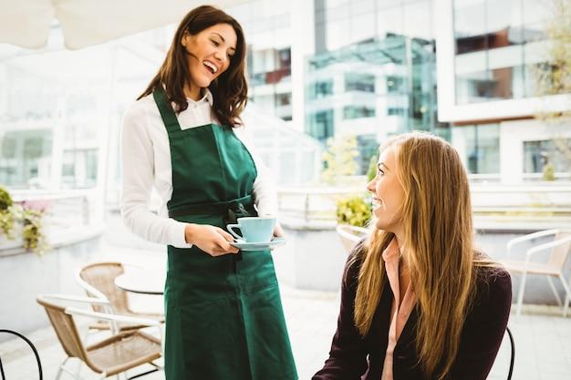 Lächelnde kellnerin, die dem kunden einen kaffee dient