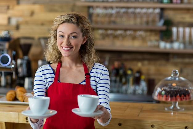 Lächelnde kellnerin, die eine tasse kaffee anbietet