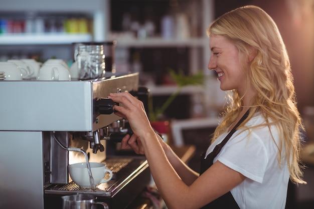 Lächelnde kellnerin, die eine tasse kaffee macht