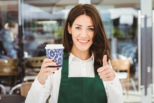 Lächelnde kellnerin, die einen kaffee im café dient