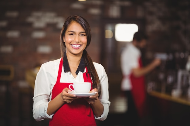 Lächelnde kellnerin, die einen tasse kaffee hält