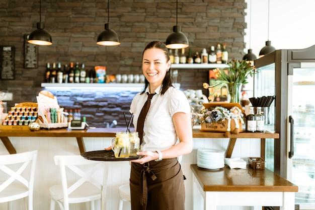 Lächelnde kellnerin mit cocktail