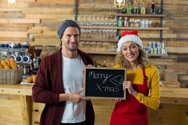 Lächelnde kellnerin und besitzer stehend mit fröhlichem weihnachtsschild im café