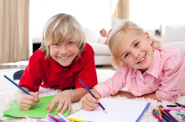 Lächelnde kinder, die das lügen auf dem boden zeichnen