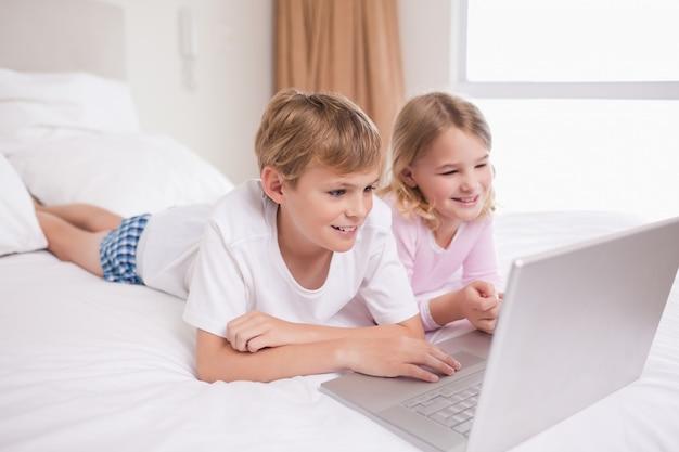 Lächelnde kinder, die ein notizbuch verwenden