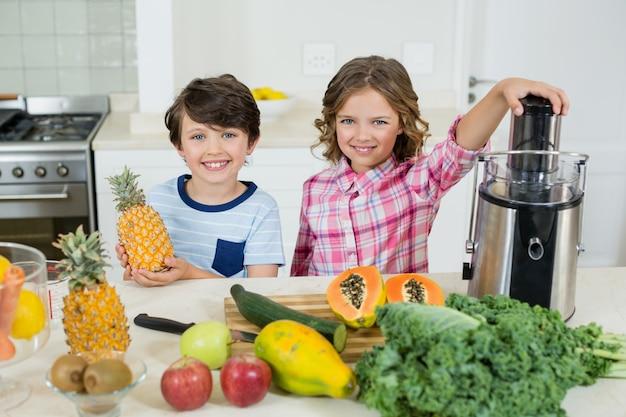 Lächelnde kinder, die einen saft in der küche vorbereiten