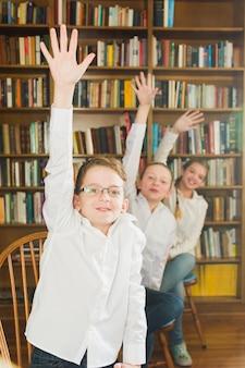 Lächelnde kinder, die hände in bibliothek setzen