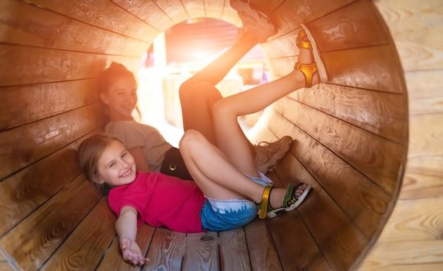 Lächelnde kinder, die in holzrohr auf sonnigem spielplatz liegen