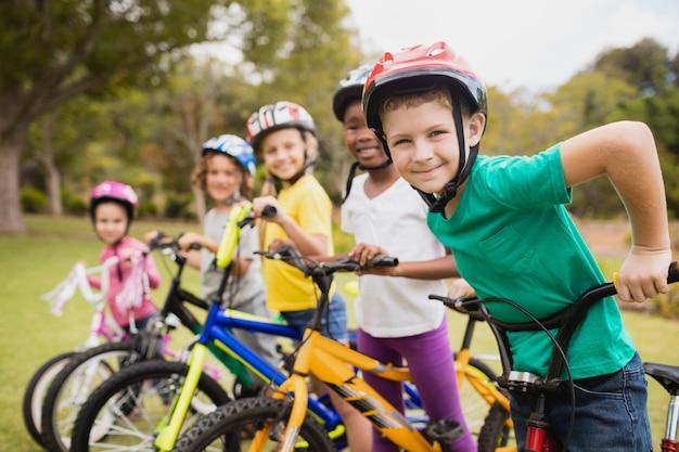 Lächelnde kinder, die in rohem mit fahrrädern aufwerfen