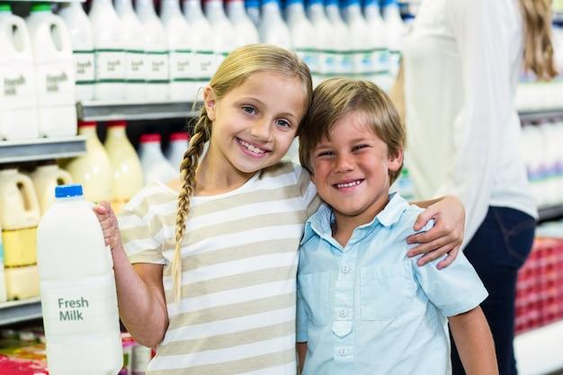 Lächelnde kinder, die milch anhalten