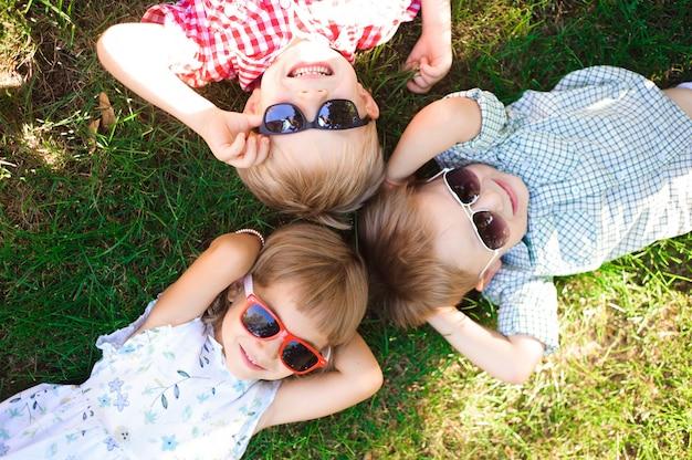 Lächelnde kinder im garten mit sonnenbrille