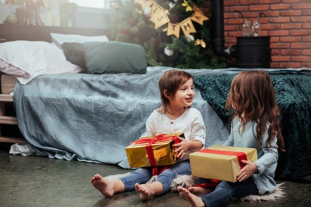 Lächelnde kinder. weihnachtsferien mit geschenken für diese beiden kinder, die drinnen im schönen zimmer neben dem bett sitzen.