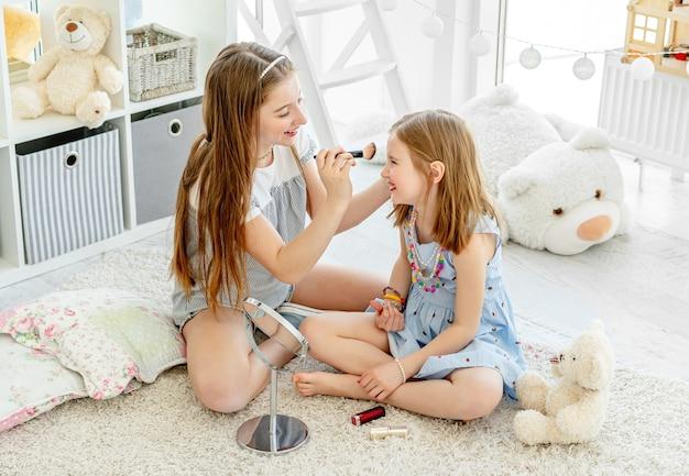 Lächelnde kindermädchen, die make-up-kosmetik im kinderzimmer anwenden