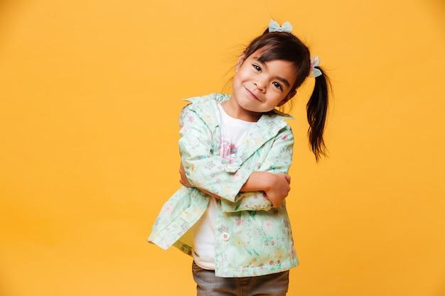 Lächelnde kindstellung des kleinen mädchens lokalisiert