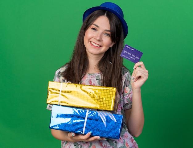 Lächelnde, kippende junge schöne frau mit partyhut, die geschenkboxen mit kreditkarte isoliert auf grüner wand hält