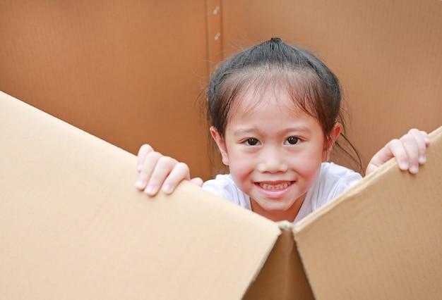 Lächelnde kleine asiatische kindermädchenlüge in der großen pappschachtel.