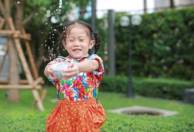 Lächelnde kleine asiatische thailändische kinder im thailändischen zeitraumkleid, das wasser im songkran festival spritzt