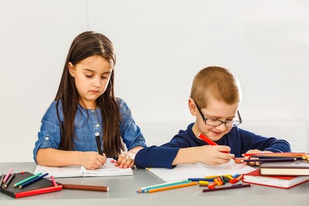 Lächelnde kleine kinder am tisch, die mit zeichenstiften zeichnen